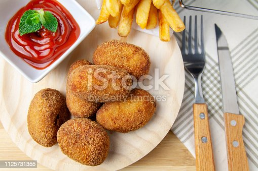 istock Upper view ham and chicken croquettes on a wood plate with tomate and chips 1125731355