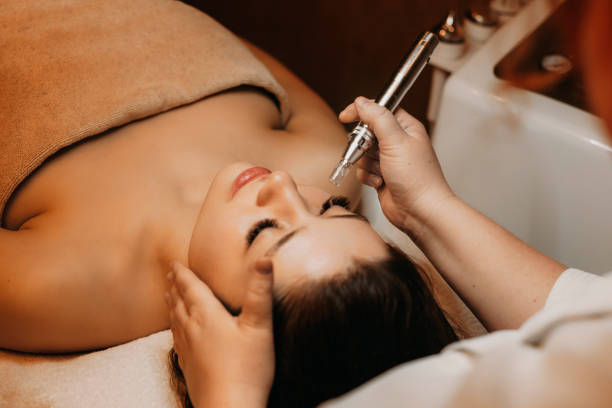Upper view of a charming brunette doing radiofrequency treatment on her face in a wellness center. stock photo