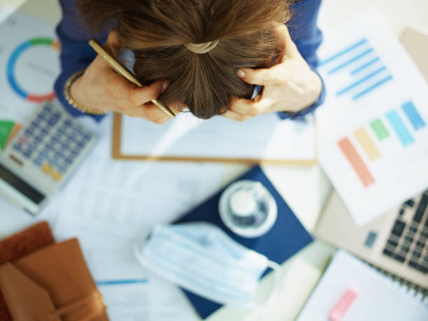 Upper view of stressed middle age business woman at table stock photo