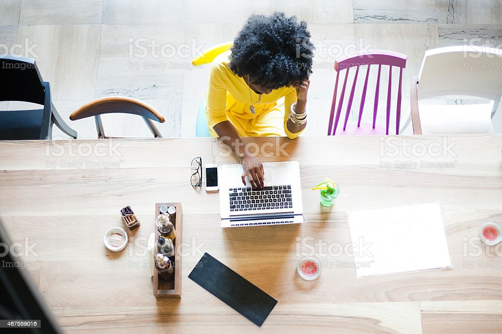 Upper view of woman sitting on a table using a laptop stock photo