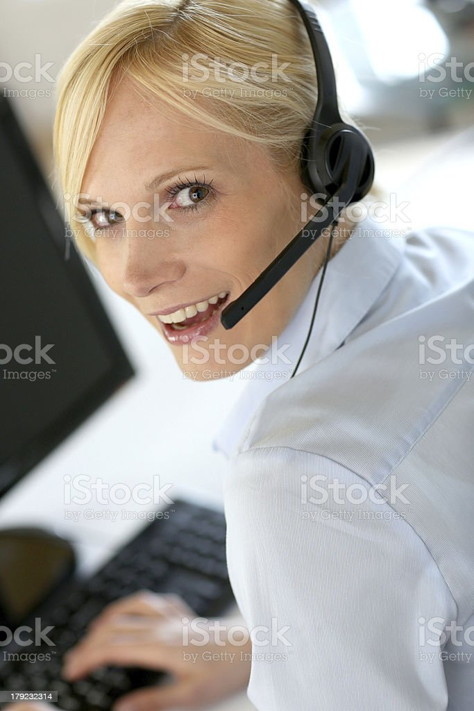 Upper view of young blonde woman working with headphone stock photo