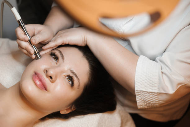 Upper view portrait of a beautiful caucasian female leaning on a bed with eyes open while having non invasive microdermabrasion on her face in a spa salon. stock photo