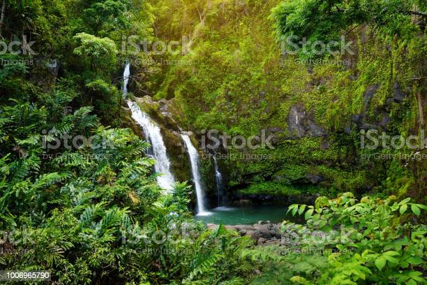 Photo of Upper Waikani Falls also known as Three Bears, a trio of large waterfalls amid rocks & lush vegetation with a popular swimming hole, Maui, Hawaii