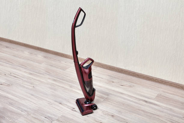 Upright red vacuum cleaner  in empty room. Handheld vacuum cleaner with a separate small dust tank in an empty room. cordless phone stock pictures, royalty-free photos & images