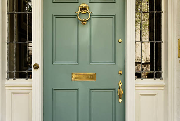 Upscale Home Front Door Front residence entrance with a classic design. The door has a large brass knocker and mail slot. Horizontal shot. front door stock pictures, royalty-free photos & images