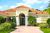 New upscale home with tile roof, lush tropical foliage and palm trees.