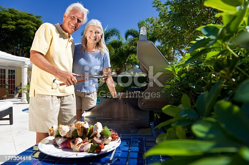 696841580istockphoto Upscale mature couple barbecuing in a lush treed environment 177304418