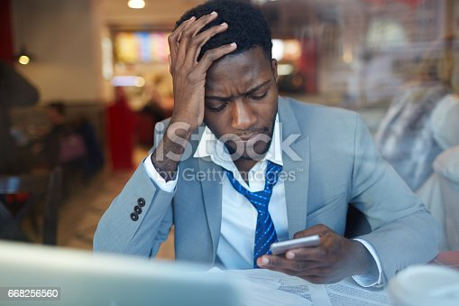 Portrait of worried African –American businessman looking stressed and resting his head on hand while typing message in smartphone sitting at counter in coffee shop, shot behind glass window