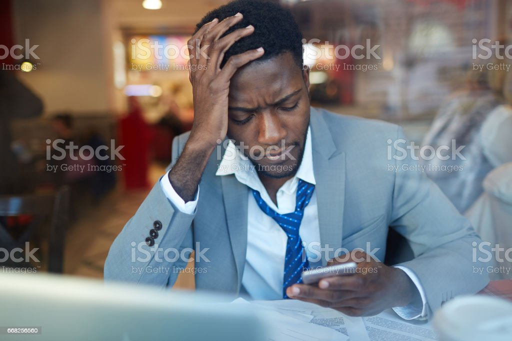 Upset African Businessman with Smartphone in Coffee Shop stock photo