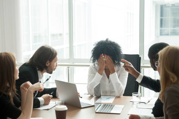 Upset african businesswoman suffering from discrimination or exhaustion at meeting Rude diverse colleagues humiliating offending stressed upset young african woman leader suffering from gender racial discrimination during meeting or feeling exhausted tired of responsibility at work sex discrimination stock pictures, royalty-free photos & images
