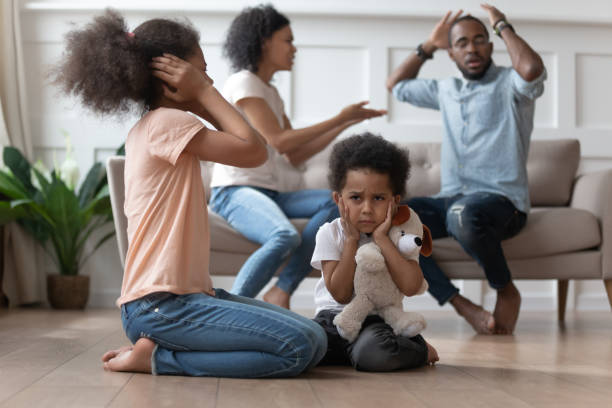Upset african kids closing ears hurt by parents fighting Upset african kids closing ears hurt by parents fighting arguing at home, sad stressed little innocent children suffer from family problems conflicts, unhappy mom dad shouting quarreling divorcing arguing stock pictures, royalty-free photos & images