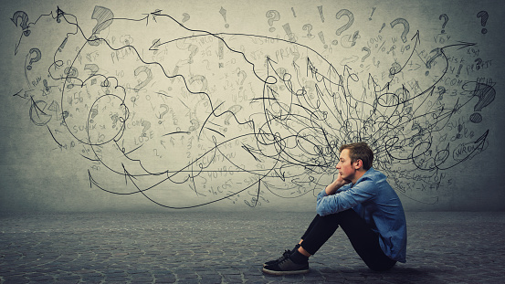 Upset And Tired Boy Teenager Sitting On The Floor Keeps Hand To Cheek Looking Thoughtfully And Hopeless Stressed Student Guy Feels Emotional Discomfort Anxiety And Mental Health Problems Stock Photo - Download Image Now