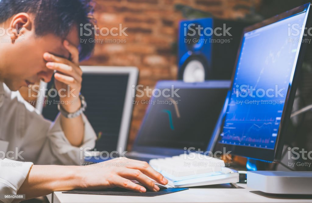 upset asian businessman at desk, depressed by working in office. feeling strain in eyes after working for long hours on computer royalty-free stock photo