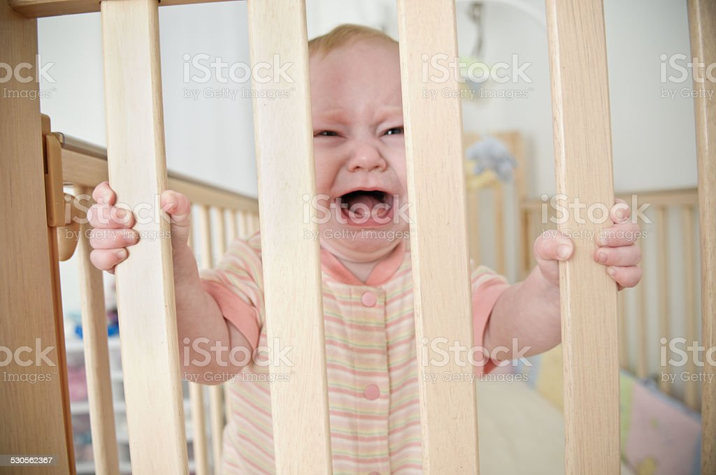 Upset Baby Girl Trapped in Crib at Home stock photo