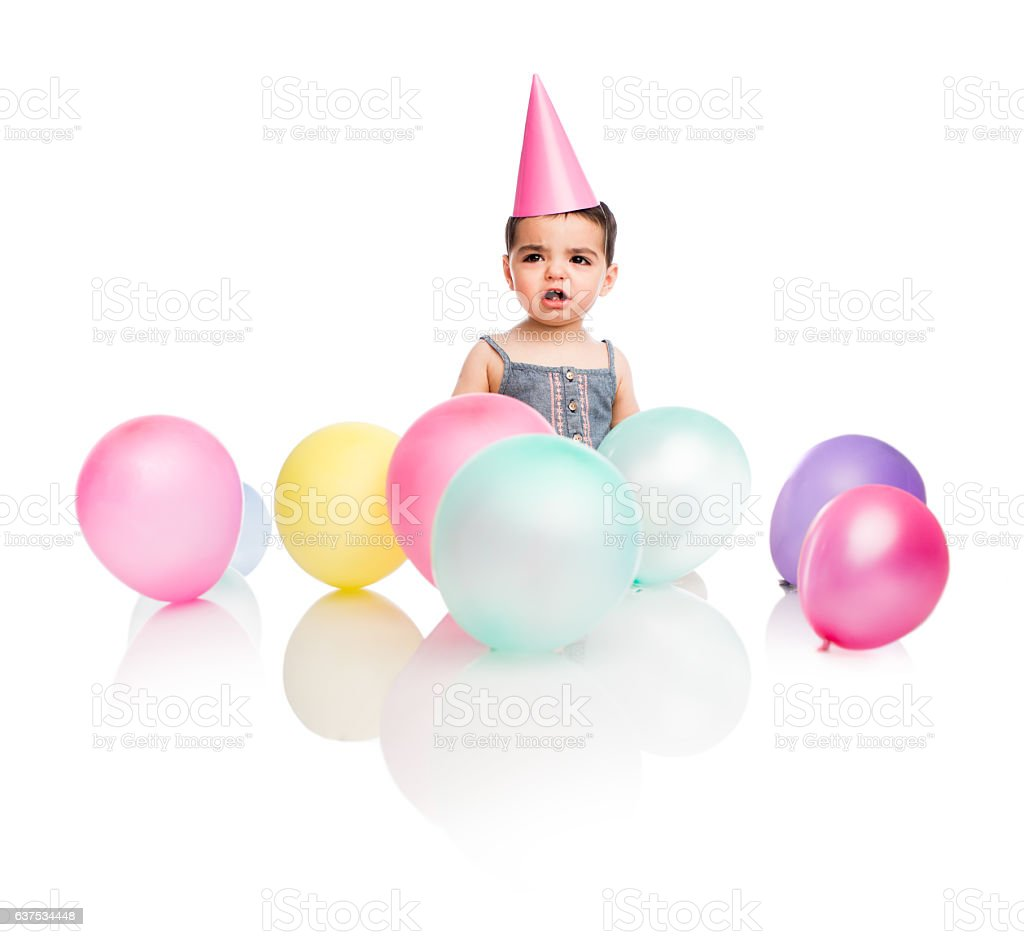 Upset baby girl with party decoration - foto de stock
