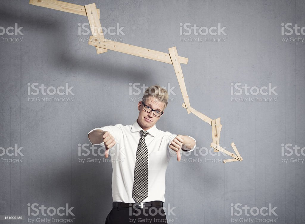 Upset businessman in front of descending graph. royalty-free stock photo