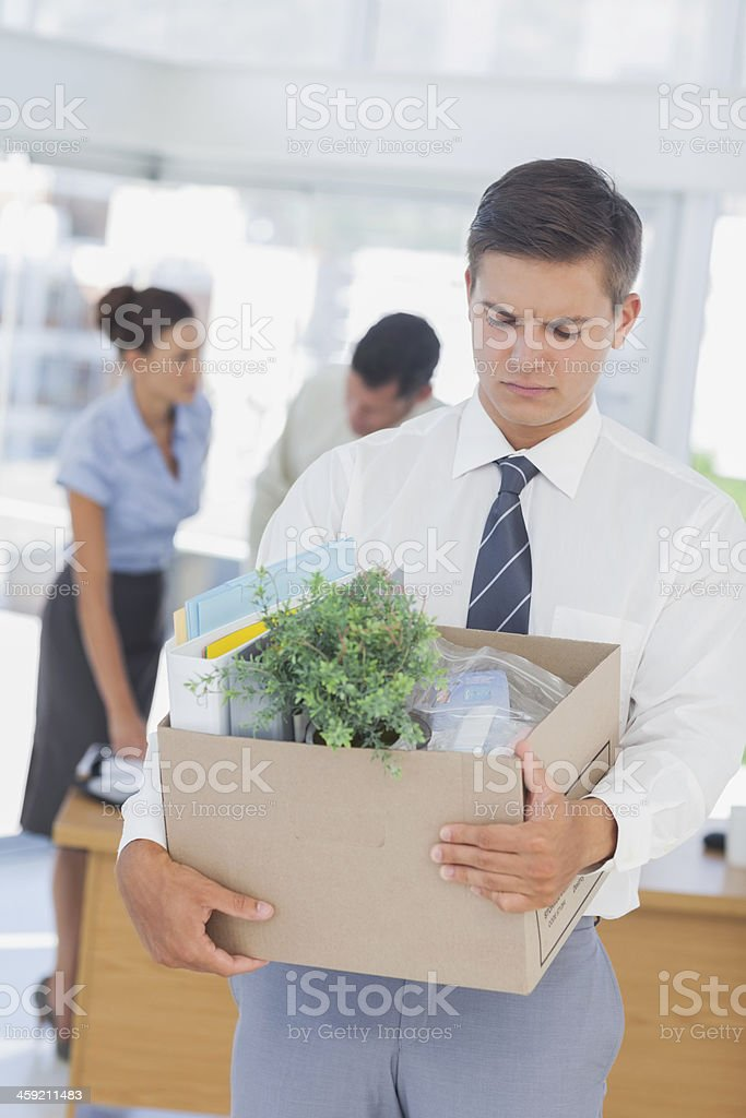 Upset businessman leaving office after being laid off stock photo