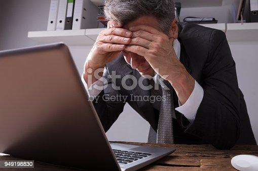 932342408istockphoto Upset Businessman Sitting In Office 949198830