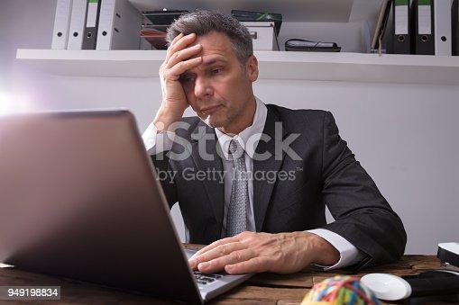 932342408istockphoto Upset Businessman Sitting In Office 949198834