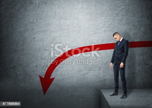 istock Upset businessman standing on the edge of abyss with red 617888994