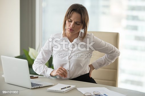 821012164istockphoto Upset businesswoman feeling back pain touching aching muscles in office 994101932
