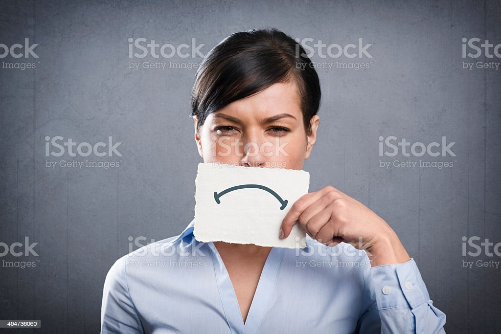 Upset businesswoman holding blank white card in front of mouth. stock photo
