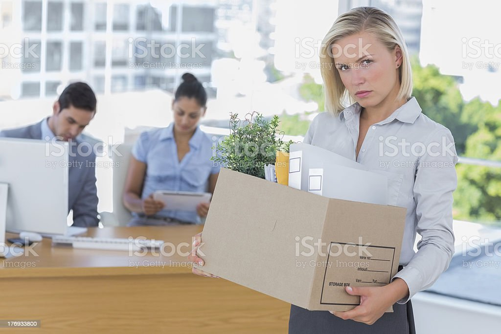 Upset businesswoman leaving office after being let go stock photo