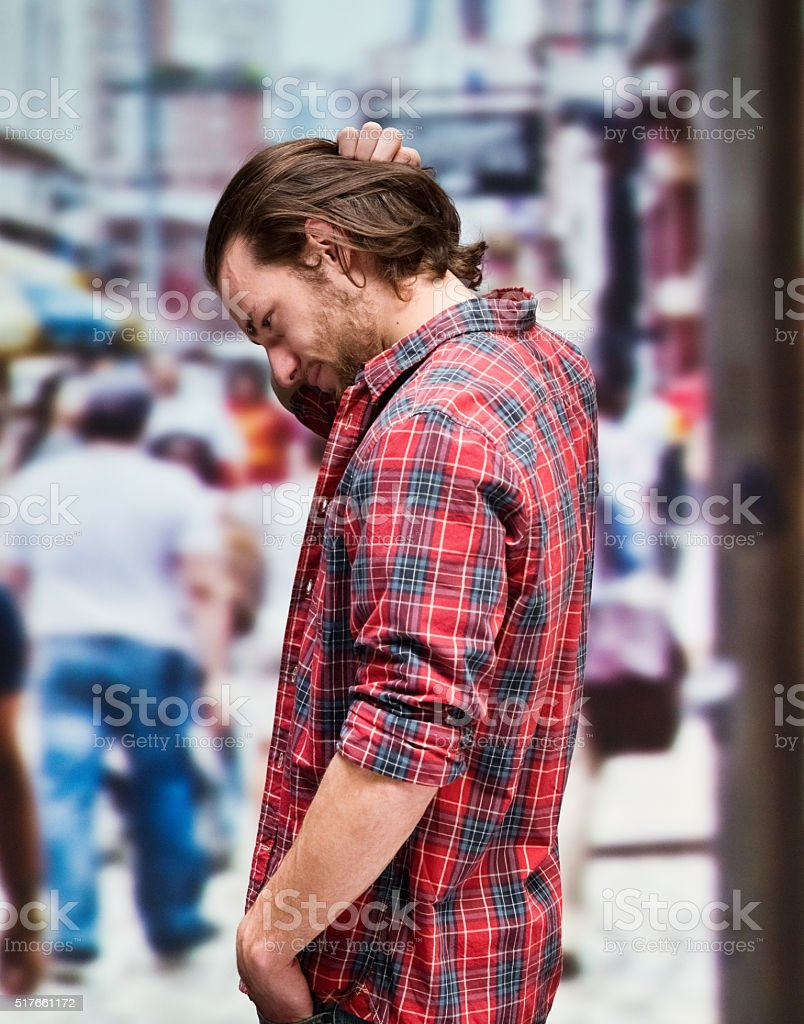 Upset casual man looking down stock photo