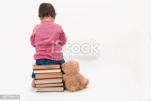 istock Upset child sitting on books with her teddybear 537794415
