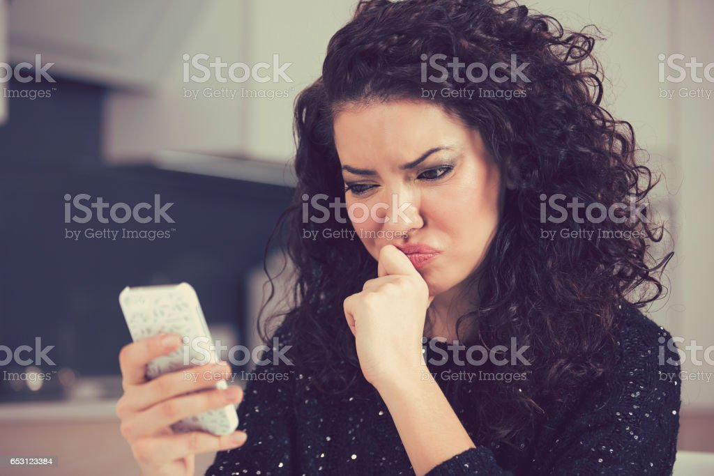 Upset confused young woman suing mobile phone reading text message stock photo