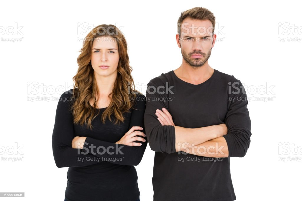 Upset couple standing with arms crossed stock photo