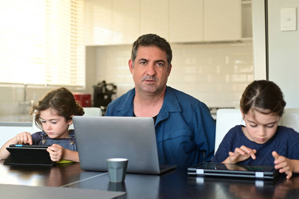 Upset displaced father forced to work from home as the pandemic coronavirus (COVID-19) forces many employees to work from home stock photo