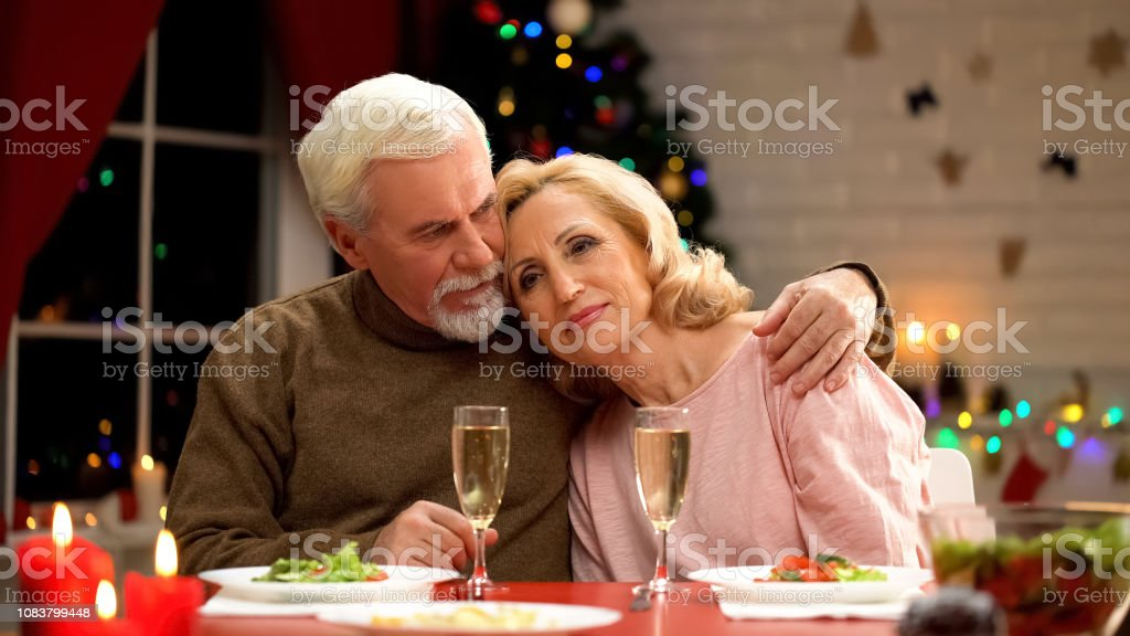 Upset elderly man and woman hugging on Christmas eve, loneliness in...