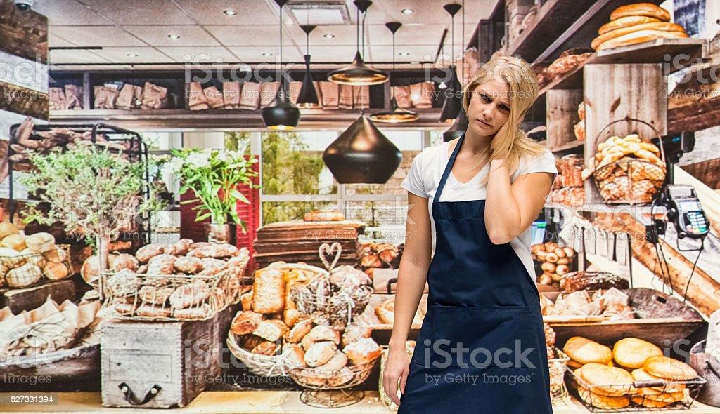 Upset female baker standing in bakery stock photo