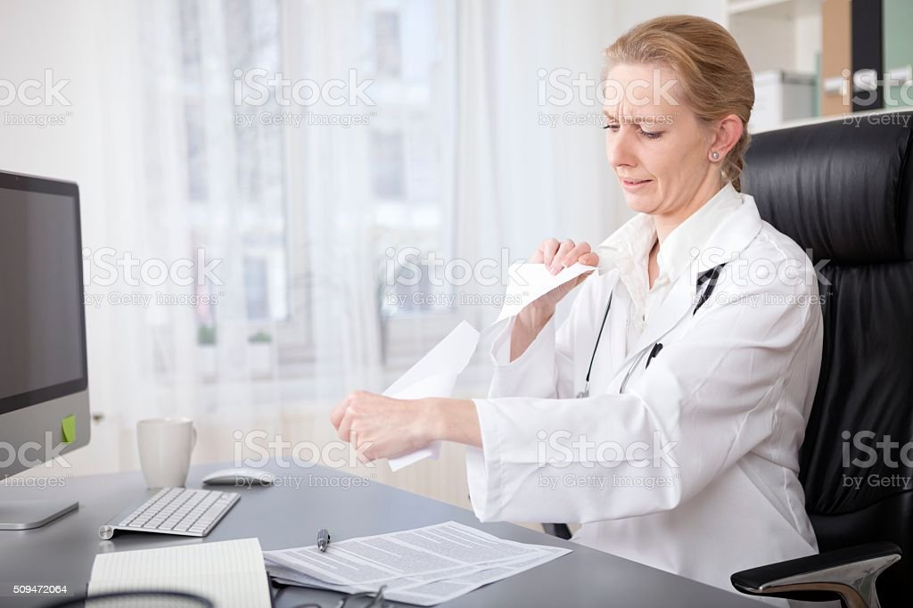 Upset Female Doctor Shredding Some Documents stock photo