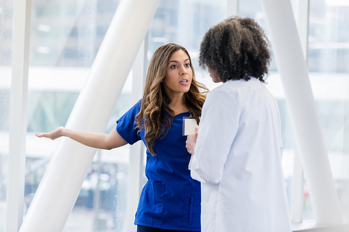 Female healthcare professionals disagree about a patient's diagnosis. A young female doctor argues with a mature female colleague. She gestures with a serious expression on her face.