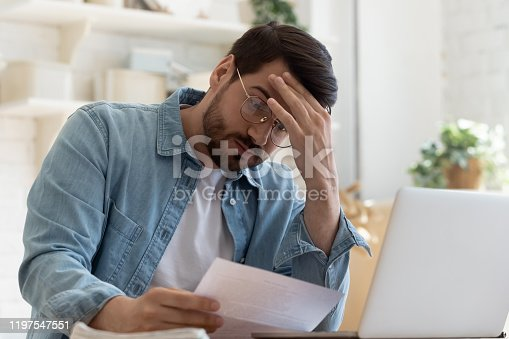 istock Upset frustrated young man holding reading postal mail letter 1197547551