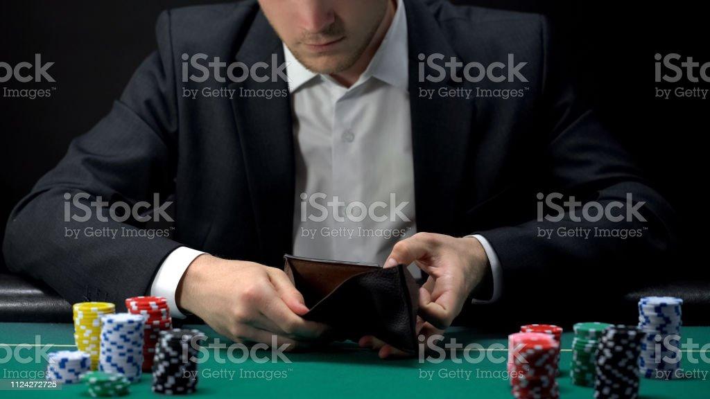 Upset gambler looking in empty wallet, loser at casino table, game...