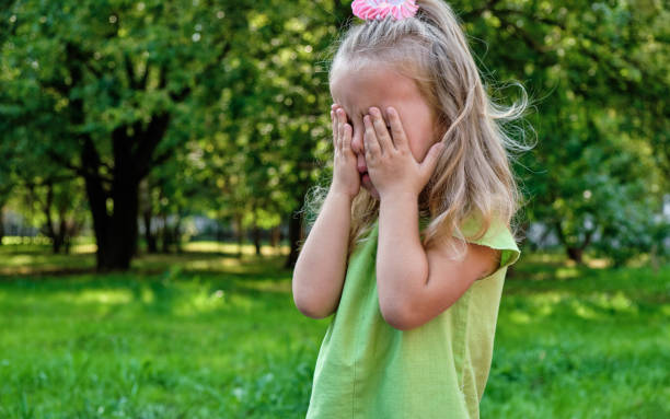 Upset girl child crying in the park. Parenting, child psychology stock photo