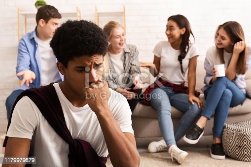 Discrimination concept. Upset guy feeling lonely, avoid talking to teens