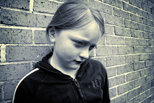 Upset girl black and white image of an upset girl leaning against a brick wall absentee stock pictures, royalty-free photos & images