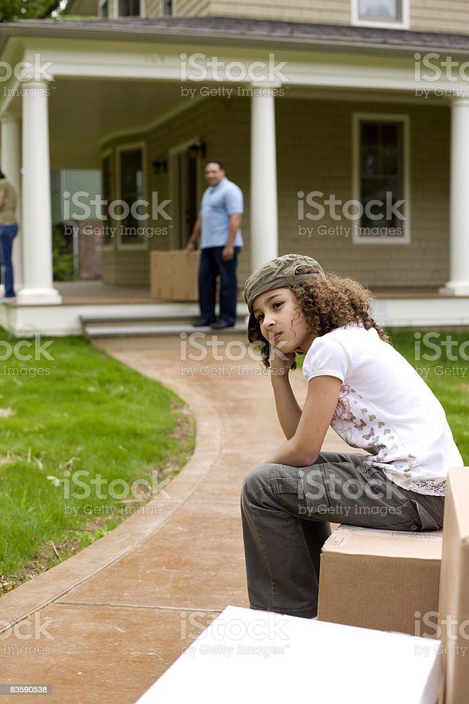 Upset girl sitting on moving boxes outside house  35-39 Years Stock Photo