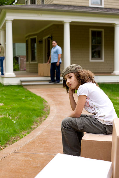 Upset girl sitting on moving boxes outside house stock photo