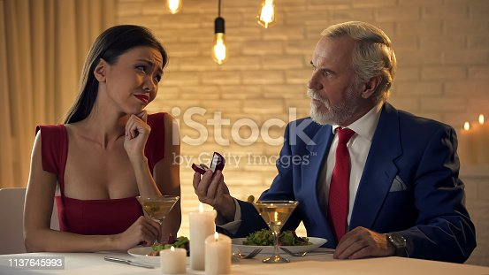 Upset girlfriend looking at jewelry gifted by elderly millionaire, mistress