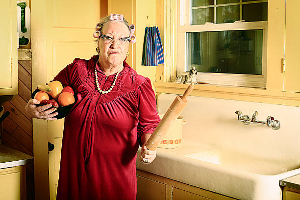 A upset grandmother standing in a kitchen holding a roller