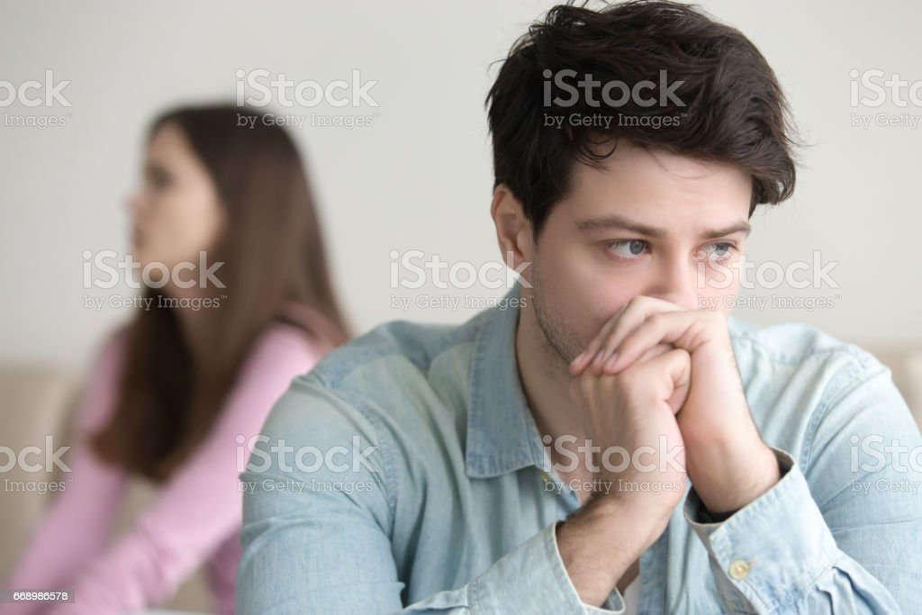 Upset guy deep in thoughts, argument with girlfriend, financial problems stock photo
