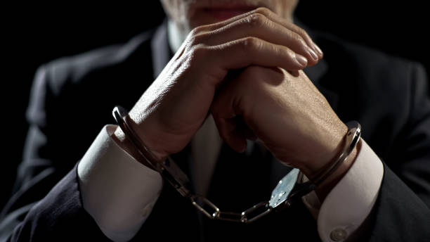 malestar hombre esposado, encarcelado por delitos financieros, castigado por fraude grave - esposa fotografías e imágenes de stock