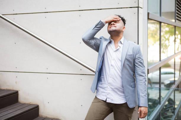 upset hispanic geschäftsmann denken probleme - migräne vorbeugen stock-fotos und bilder