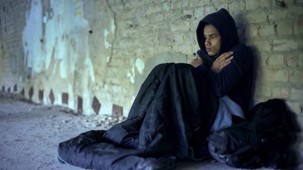 perturbado adolescente sem-teto usando capuz, a sensação de frio, a indiferença e a pobreza - sem teto - fotografias e filmes do acervo