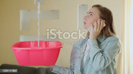 1164292968 istock photo Upset household calling roof repair service while water leaking from ceiling 1235141852